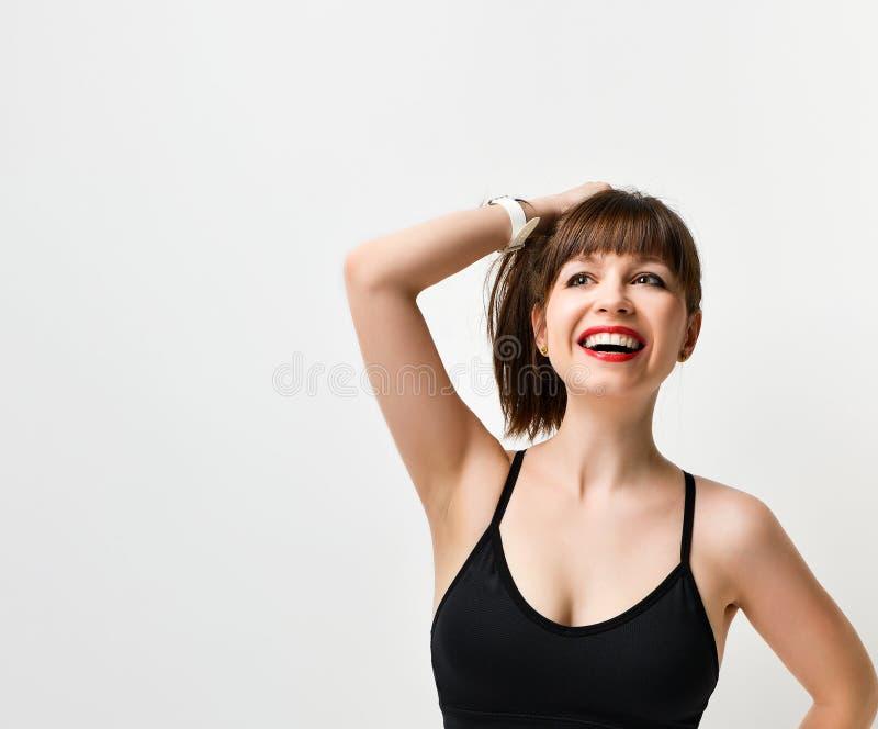 Portret brunetki Młoda dziewczyna w czerni bawi się podkoszulek bez rękawów, na białym tle fotografia stock