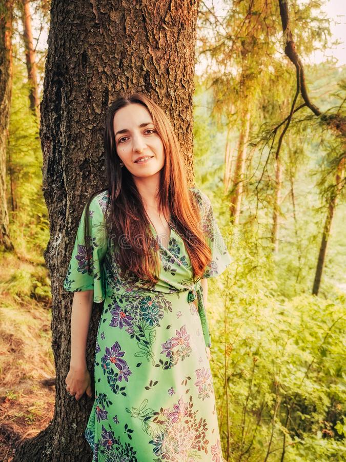 Portret brunetki piękna uśmiechnięta caucasian dziewczyna z długie włosy w lesie przy zmierzchem opierał z powrotem przeciw drzew zdjęcia royalty free
