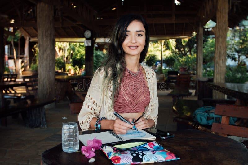 Portret brunetki piękna kobieta ono uśmiecha się przy drewnianym stołem w lato kawiarni obraz royalty free