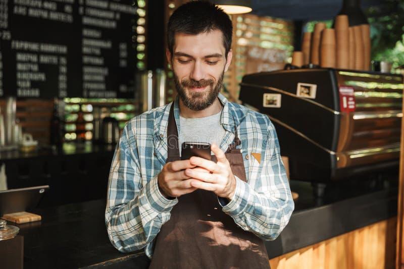 Portret caucasian barista facet pisać na maszynie na telefonie komórkowym w ulicznej kawiarni lub coffeehouse plenerowy obraz royalty free