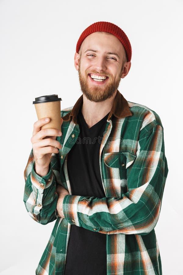 Portret caucasian brodaty facet jest ubranym kapeluszu i szkockiej kraty koszula trzyma papierową filiżankę z kawą, podczas gdy s obrazy stock