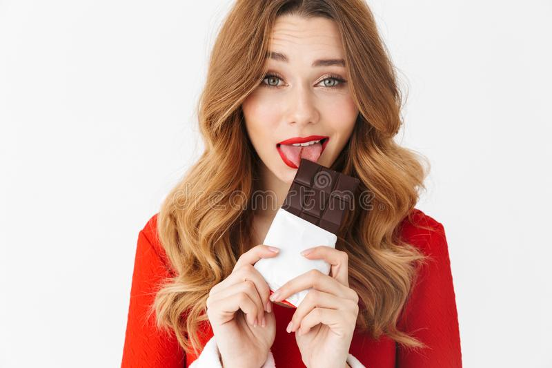 Portret caucasian kobieta 20s jest ubranym Święty Mikołaj czerwony kostiumowy ono uśmiecha się i je czekoladowego baru, odosobnio zdjęcie stock