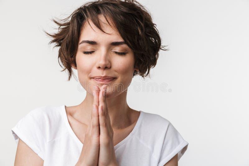 Portret caucasian kobieta utrzymuje palmy i ono modli się wpólnie z krótkim brązu włosy w podstawowej koszulce fotografia stock