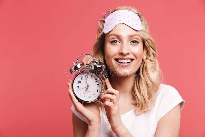 Portret caucasian m?oda kobieta 20s jest ubranym sypialnego maskowego mienie budzika po obudzi? fotografia stock