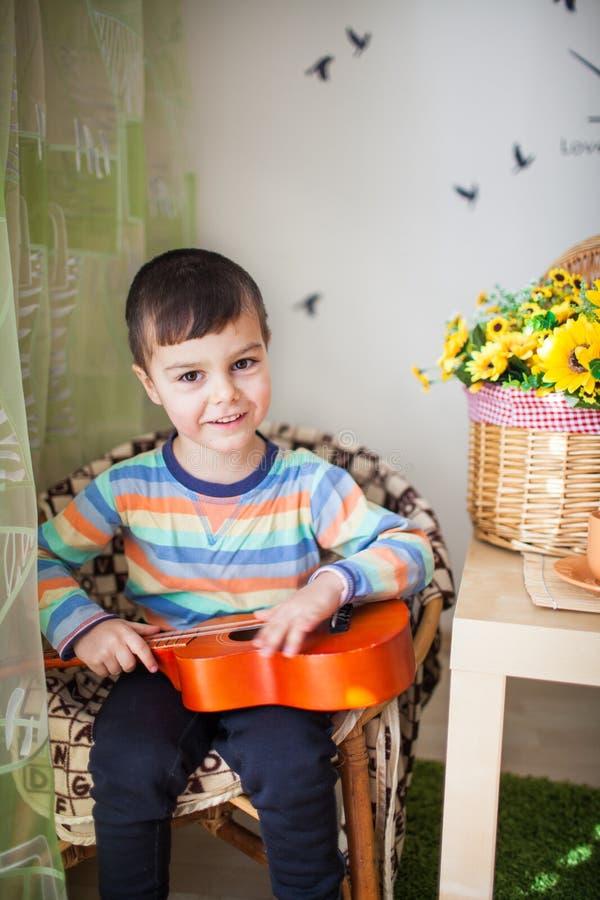 Portret caucasian mała powabna chłopiec z zabawkarską gitarą w selekcyjnej ostrości zdjęcie stock