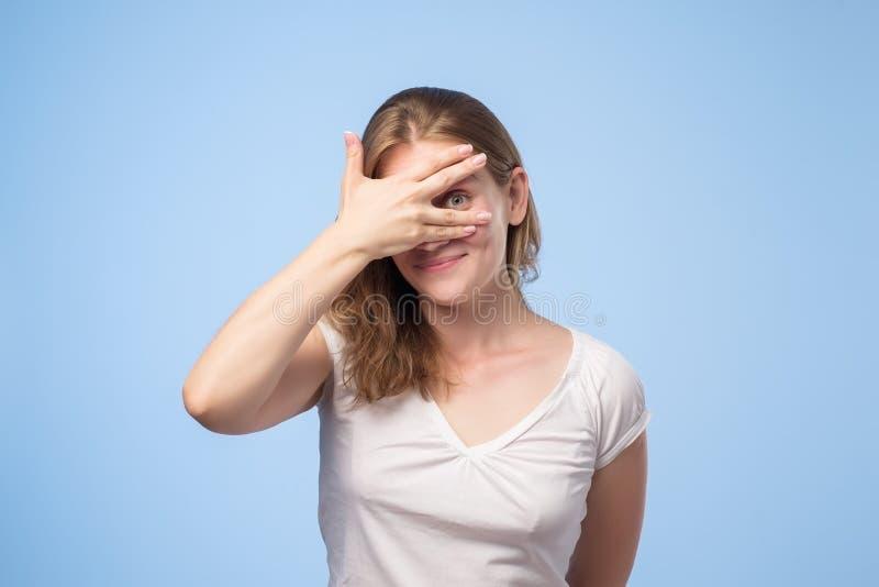 Portret caucasian w średnim wieku kobieta w białym koszula zakończeniu ona oczy z palmą, spoglądanie, zerkanie out zdjęcie stock