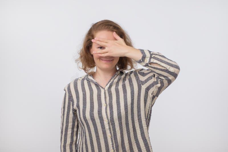 Portret caucasian w średnim wieku kobiety zakończenie ona oczy z palmą, spoglądanie, zerkanie otwarci palce na jeden ręce out obraz stock