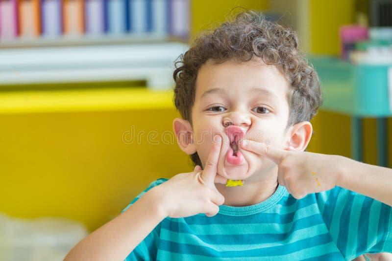 Portret Caucasious chłopiec sztuka zabawy twarz w sala lekcyjnej przy kinde zdjęcie royalty free