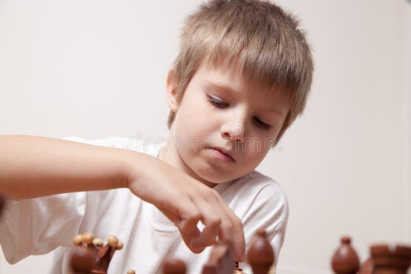 Portret chłopiec bawić się szachy zdjęcie stock