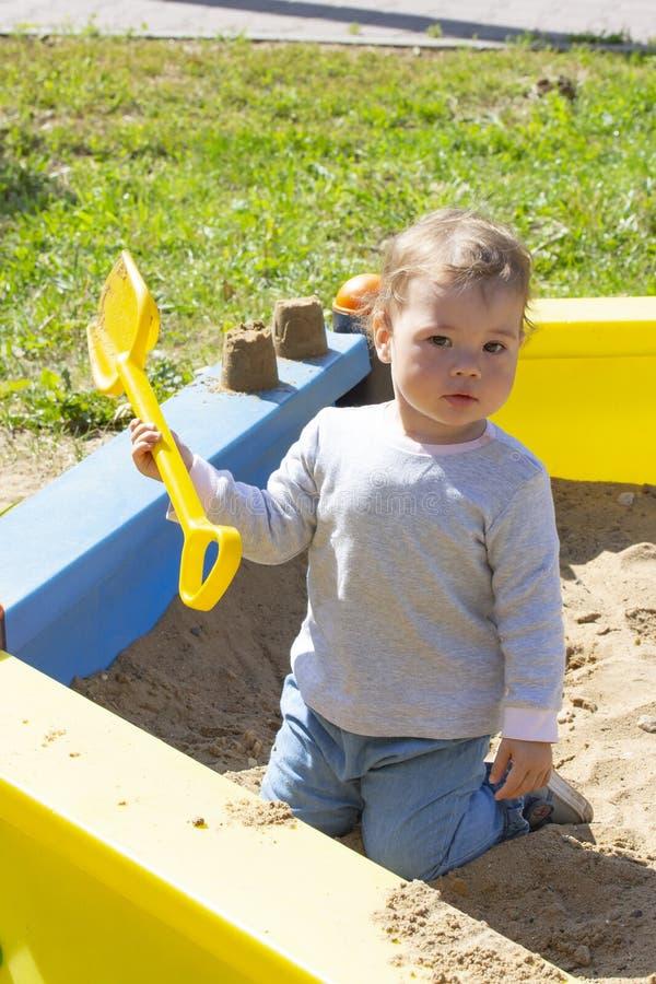 Portret chłopiec dziewczyna bawić się w piaskownicie z żółtą plastikową łopatą troszkę Śliczny dzieciak na spacerze bawić się z p obrazy stock