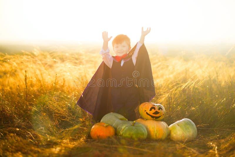 Portret chłopiec ubierająca jako Dracula outdoors w dyniowej łacie na zmierzchu tle troszkę halloween zdjęcie stock