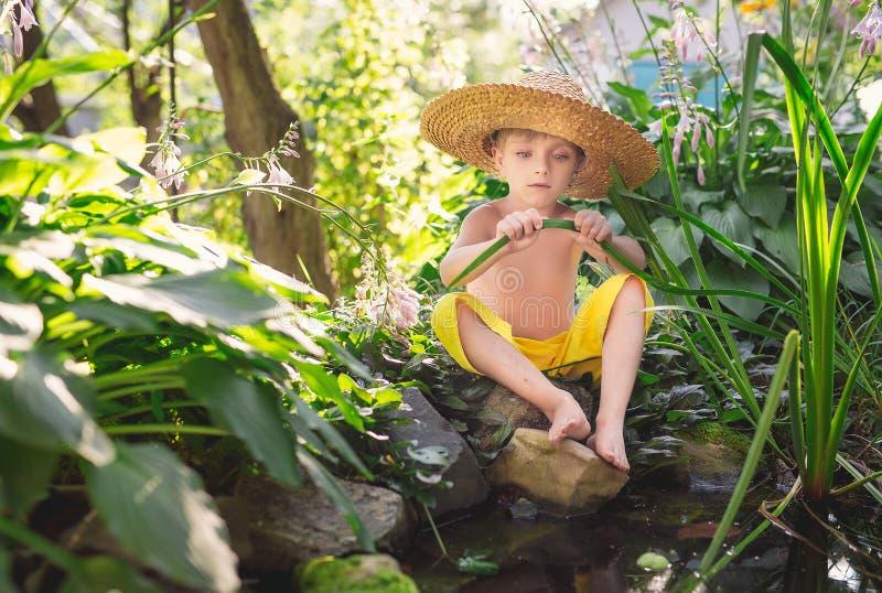 Portret chłopiec w słomianym kapeluszu i kolorze żółtym dyszy na brzeg staw w zielonej trawie fotografia stock