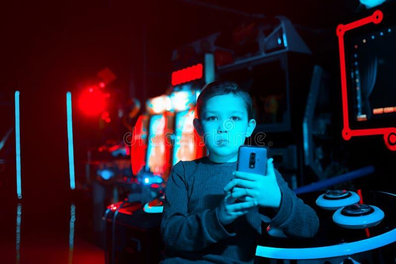 Portret chłopiec z telefonem w jego ręki kamery target982_0_ Neonowy oświetlenie Mobilne gry Gry na smartphone zdjęcie royalty free