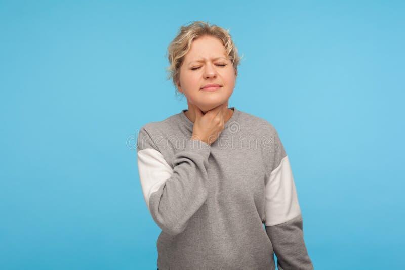 Portret chorej nieszczęśliwej dorosłej kobiety z kręconymi włosami w bluzie dotykającej szyi cierpiącej na ból gardła, bolesne po zdjęcie stock