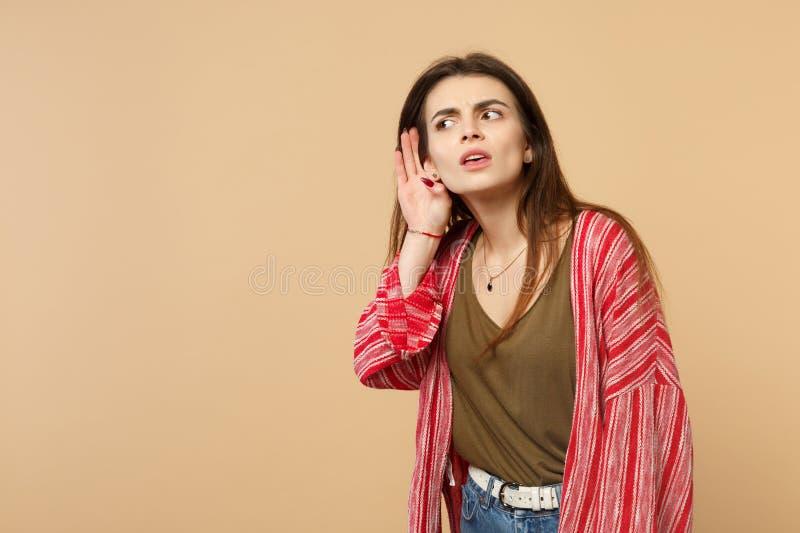 Portret ciekawa młoda kobieta w przypadkowych ubraniach podsłuchuje z przesłuchanie gestem odizolowywającym na pastelowej beż ści zdjęcia royalty free