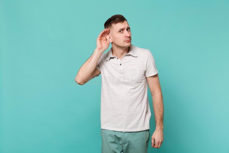 Portret ciekawy młody człowiek w przypadkowych ubraniach podsłuchuje z przesłuchanie gestem odizolowywającym na błękitnej turkus  zdjęcia royalty free