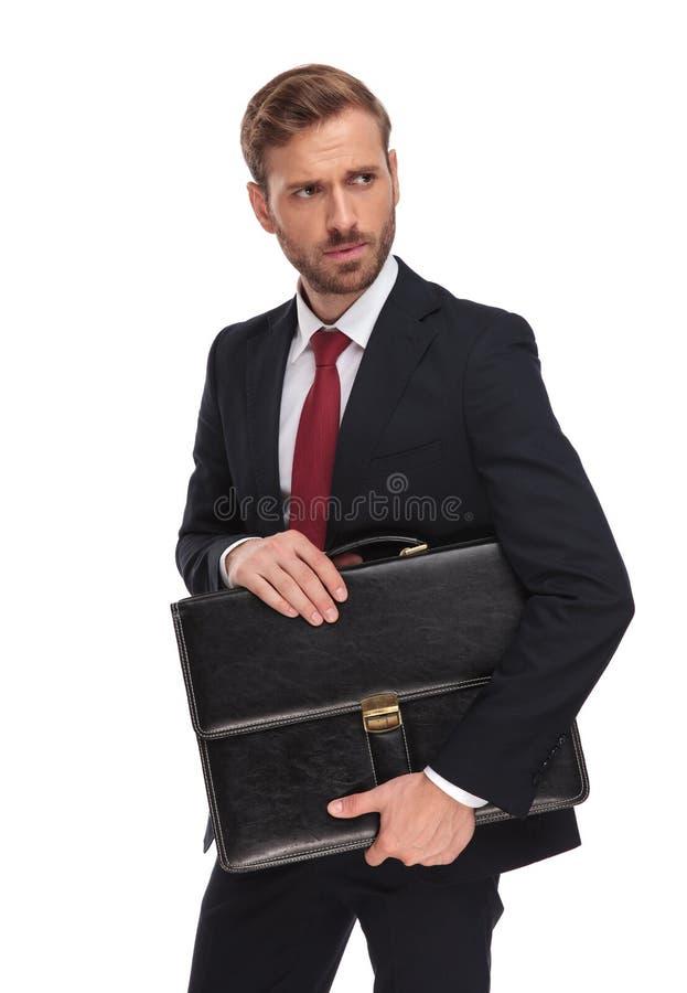 Portret ciekawy młody biznesmen trzyma walizkę zdjęcia stock