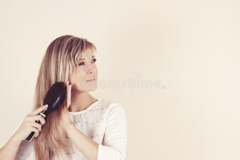 Portret czesze jej ono uśmiecha się i włosy piękna młoda kobieta zdjęcie royalty free