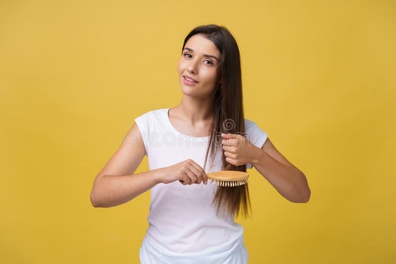 Portret czesze jej włosy piękna młoda kobieta, patrzejący kamerę i ono uśmiecha się fotografia royalty free