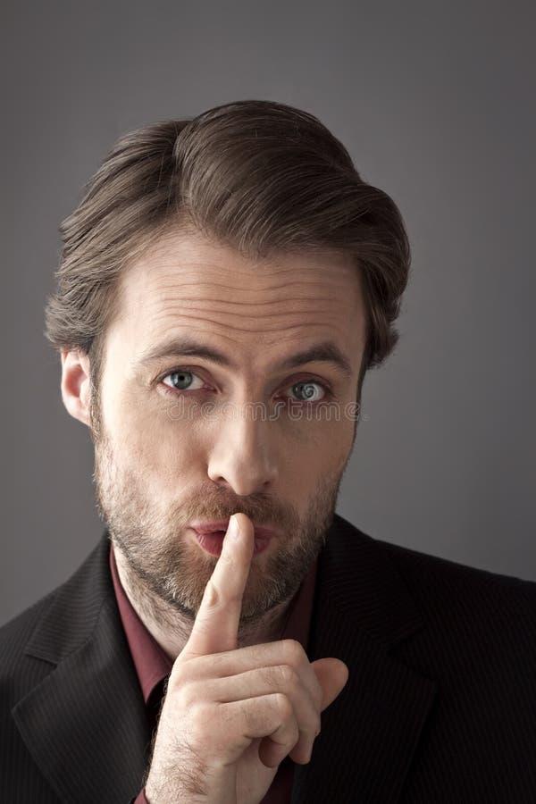 Biznesmen próbuje chować sekret z palcem na jego wargach zdjęcia stock