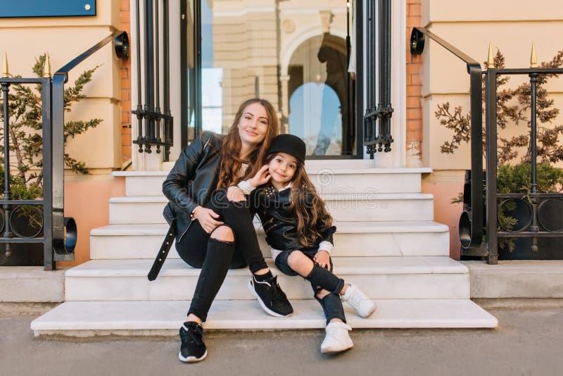 Portret długowłosa śliczna kobieta i mała dziewczynka w modnych sneakers pozuje, podczas gdy siedzący na krokach piękno obraz royalty free