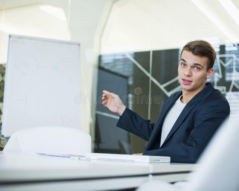 Portret daje prezentaci przy konferencyjnym stołem młody biznesmen fotografia royalty free