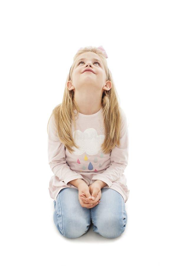 Portret dat van een aanbiddelijke meisjezitting op de knieën, omhoog kijkend op exemplaarruimte kijkt stock afbeeldingen