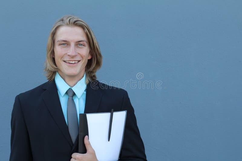 Portret dat van een knappe jonge mens, een kostuum draagt Geïsoleerd op blauw Studio met ruimte voor exemplaar en tekst wordt ges stock foto