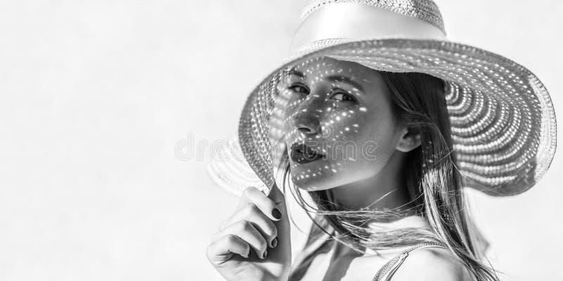 Portret dat van mooie sensuele donkerbruine jonge vrouw die met make-up camera met hartstocht bekijkt, hoed, licht door hoed houd royalty-vrije stock foto's