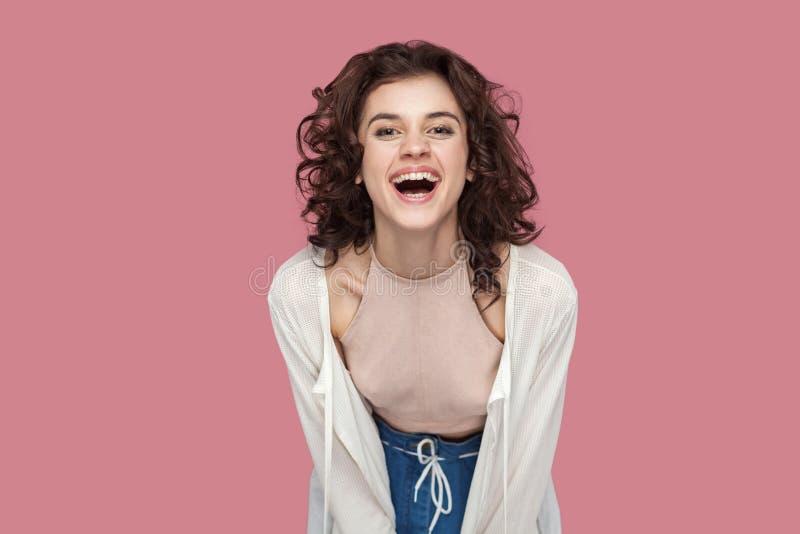 Portret dat van opgewekte gelukkige positieve mooie donkerbruine jonge vrouw met krullend kapsel in toevallige stijl die, camera  royalty-vrije stock afbeelding
