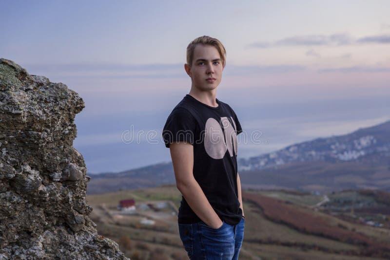 Portret in de groei Jonge aantrekkelijke mens die zich op de bovenkant van bergen bevinden stock afbeelding