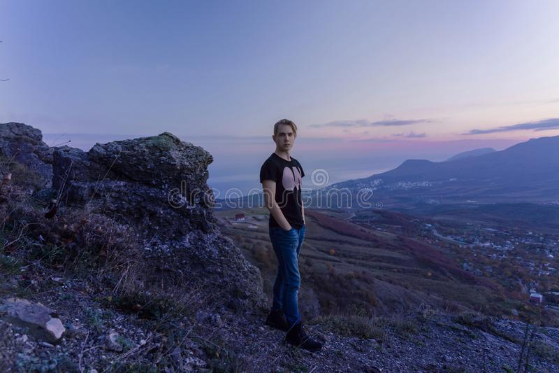 Portret in de groei De jonge aantrekkelijke mens die zich op de bovenkant van bergen bevinden kijkt aan de camera stock foto