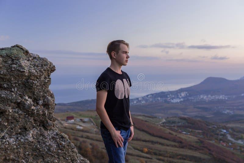 Portret in de groei De jonge aantrekkelijke mens die zich op de bovenkant van bergen bevinden onderzoekt de afstand stock afbeeldingen