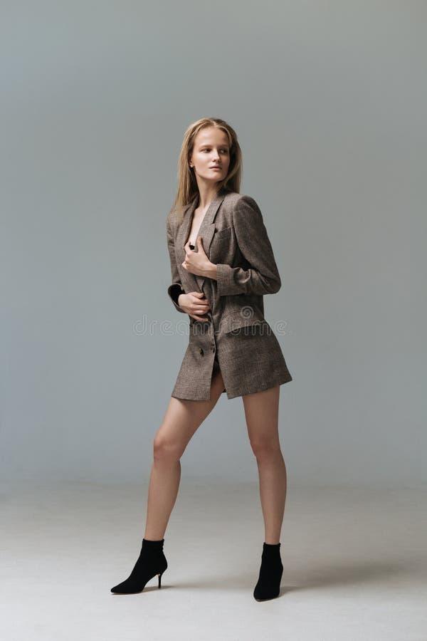 Portret de jonge elegante vrouw van gemiddelde lengte in bruin jasje royalty-vrije stock afbeelding