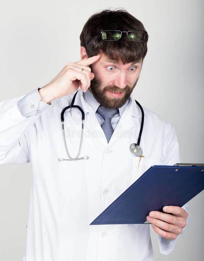 Portret del primer de un doctor que sostiene un mapa-caso para la nota, estetoscopio alrededor de su cuello Él tuerce su dedo índ imagen de archivo libre de regalías
