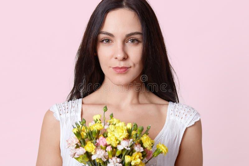 Portret delikatna brunetki młoda dama, ubierający w biel sukni, otrzymywa prezent na urodziny, fotografujący z poważny twarzowym obraz stock