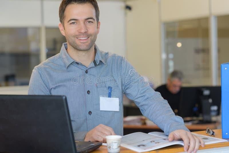 Portret die de jonge mens glimlachen die aan laptop werken terwijl het zitten royalty-vrije stock afbeelding