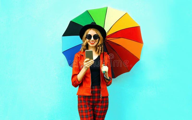 Portret die de jonge telefoon van de vrouwenholding met kleurrijke paraplu in rood jasje, zwarte hoed op blauwe muur glimlachen royalty-vrije stock afbeeldingen