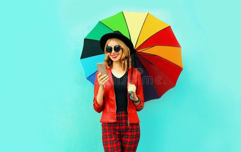 Portret die de jonge telefoon van de vrouwenholding met kleurrijke paraplu in rood jasje, zwarte hoed op blauwe muur glimlachen stock foto