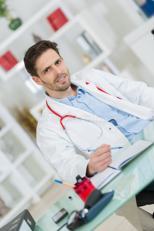 Portret die jonge mannelijke arts glimlachen stock afbeeldingen
