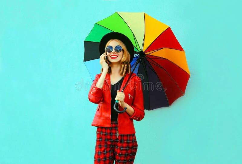 Portret die jonge vrouw glimlachen die telefoon met kleurrijke paraplu in rood jasje, zwarte hoed op blauwe muur uitnodigen stock fotografie