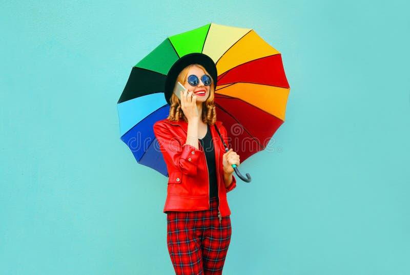 Portret die jonge vrouw glimlachen die telefoon met kleurrijke paraplu in rood jasje, zwarte hoed op blauwe muur uitnodigen stock afbeeldingen