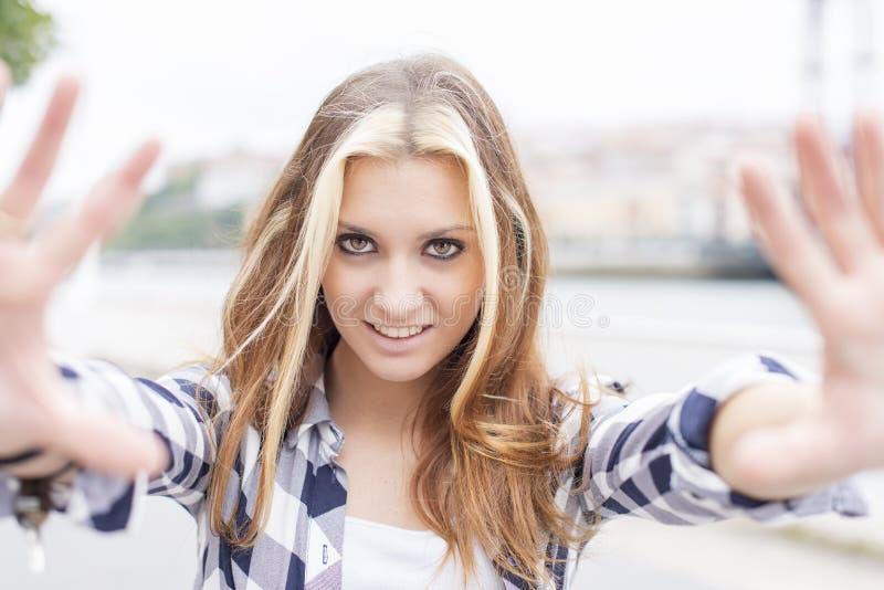 Portret die jonge vrouw met open handen naar de camera glimlachen stock foto's