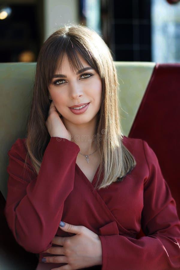 Portret die jonge vrouw met vriendschappelijke glimlach charmeren, lange donkerbruine haar het glimlachen koffie royalty-vrije stock foto