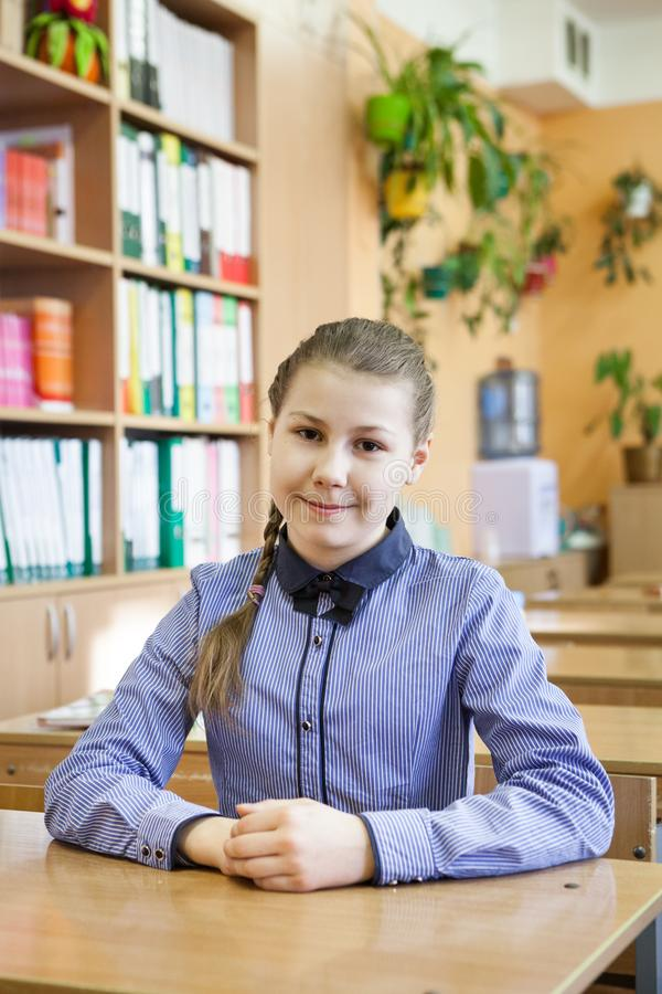 Portret die van één Kaukasische schoolmeisjezitting bij lijst in klasse, camera bekijken stock afbeeldingen