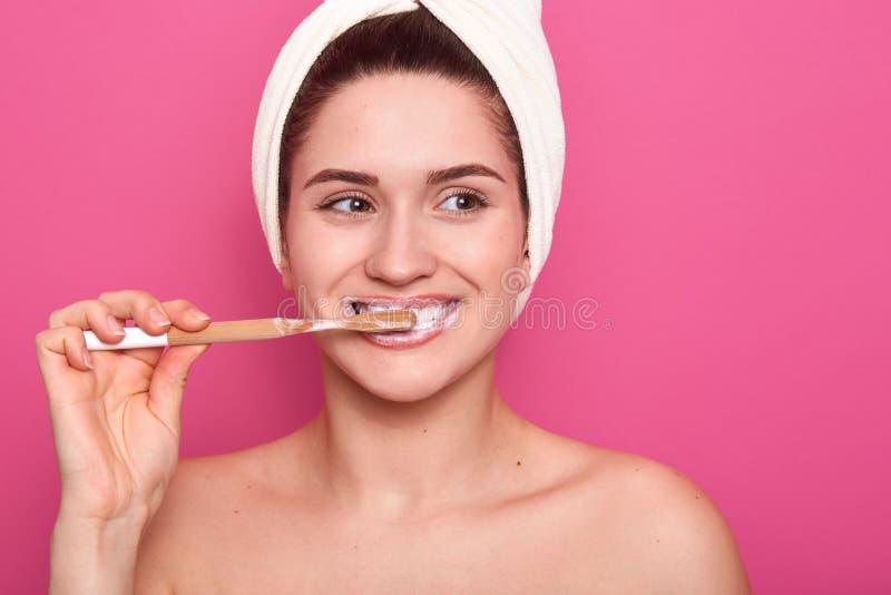 Portret die van aantrekkelijke Kaukasische glimlachende vrouw die haar tanden over roze studiomuur borstelen, met witte handdoek  stock fotografie