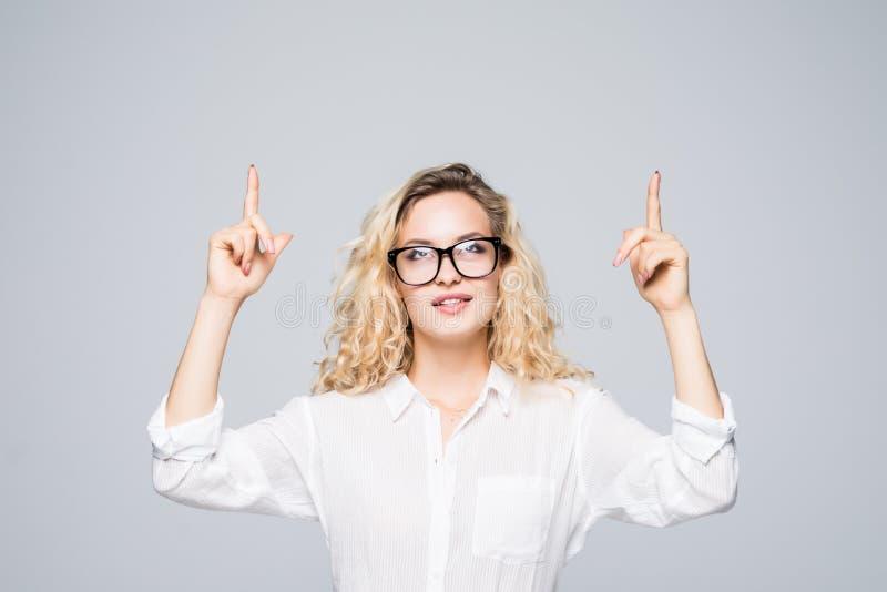 Portret die van bedrijfsvrouw, twee wijsvingers op lege plaats benadrukken, die exemplaarruimte bekijken, op grijze achtergrond w stock foto