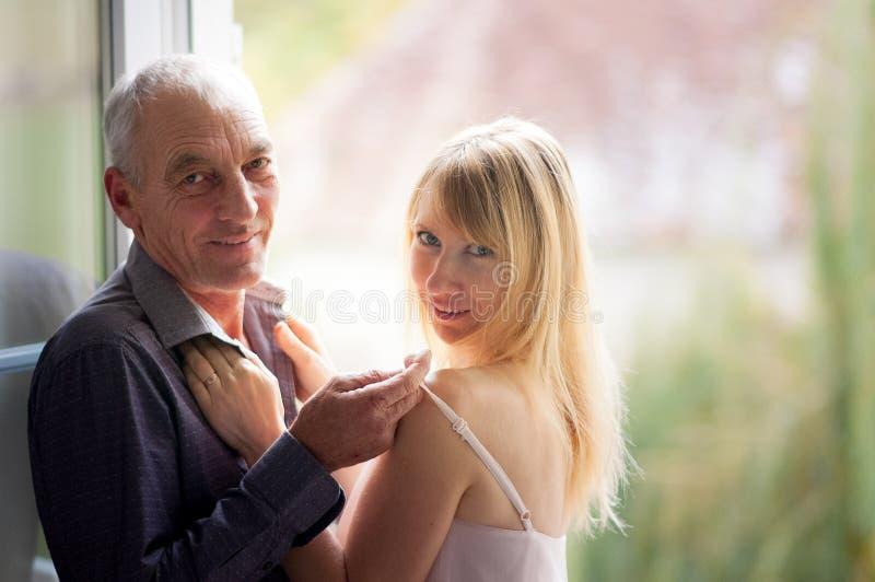 Portret die van Bejaarde zich dichtbij het Venster met Zijn Jonge blonde-Haired Vrouw in de Zomer Korte Kleding bevinden Paar met stock fotografie