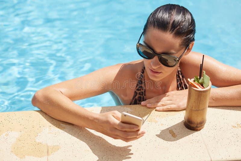 Portret die van bezig knap brunette in zwembad blijven, haar smartphone in één hand houden, typend berichten, het besteden stock foto
