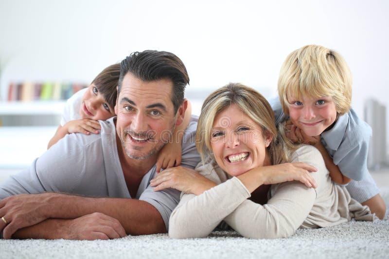 Portret die van blije gelukkige familie op tapijtvloer liggen royalty-vrije stock fotografie